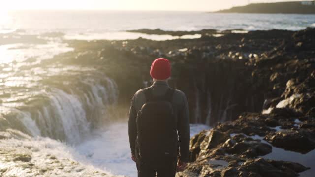 man looking at sea flow into rock pool - eskapismus stock-videos und b-roll-filmmaterial