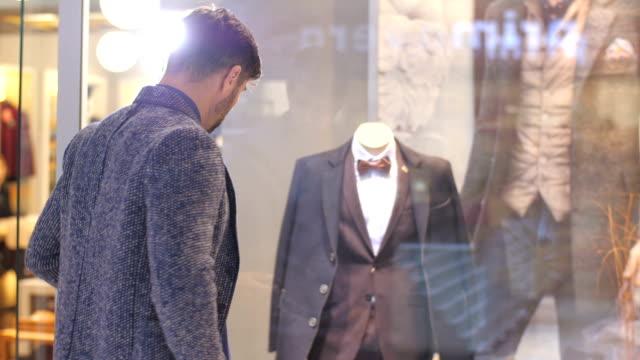 vídeos de stock, filmes e b-roll de homem que olha o terno em uma janela de loja - boutique