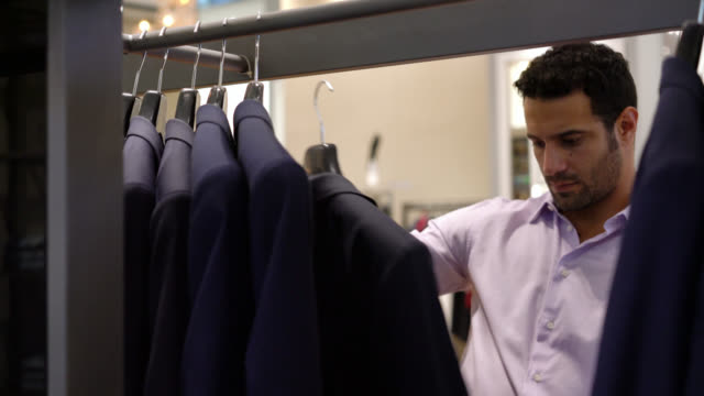 man looking at suits on a rack and trying a jacket on - vendita al dettaglio video stock e b–roll