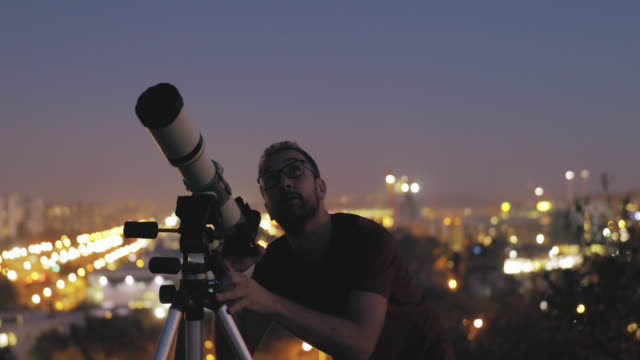 Man looking at the sky with astronomical telescope in urban surroundings.