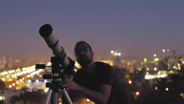 vídeos de stock, filmes e b-roll de homem que olha o céu com telescópio astronômico em arredors urbanos. - hobbie