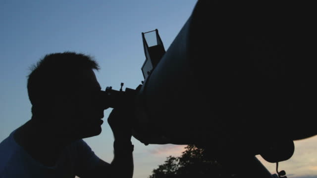 Man looking at the stars with telescope. video