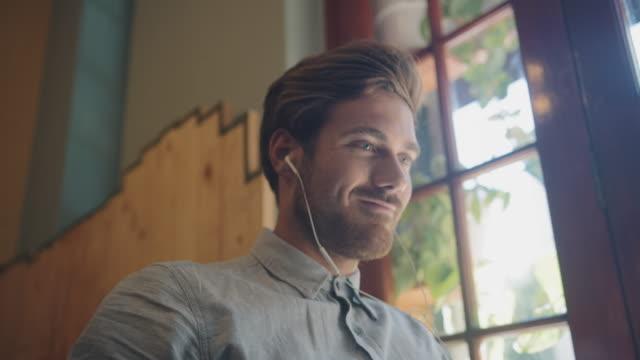 man tittar på video i café - videor med headphones bildbanksvideor och videomaterial från bakom kulisserna