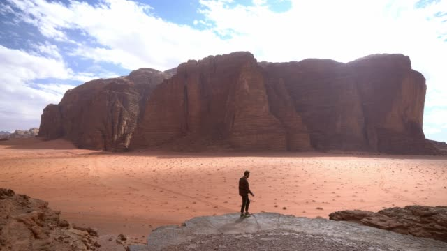 man looking at  wadi rum desert from rock - rock formations stock videos & royalty-free footage