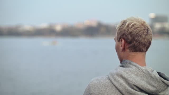 강에서 보트를 조정하는 여자를 보고 있는 남자 - 초점 이동 스톡 비디오 및 b-롤 화면