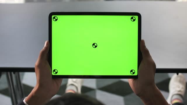 Man looking Digital tablet green screen