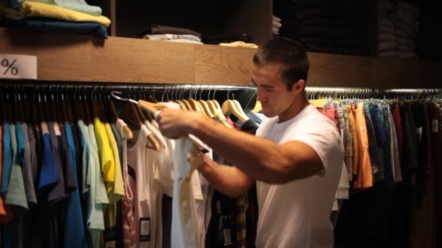 stockvideo's en b-roll-footage met man op zoek naar nieuwe casual kleding - t shirt