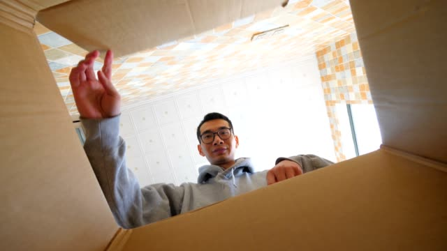 man looking inside box finding his surprise gift - avvicinarsi video stock e b–roll