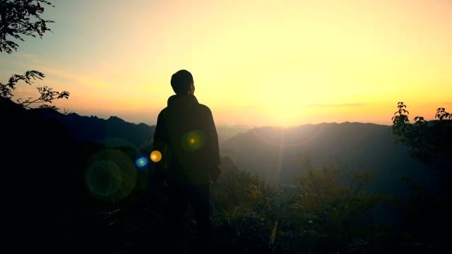 Man looking mountains sunset