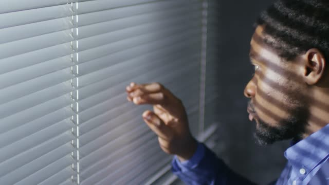 Man Looking Out of Window through Blinds