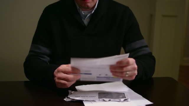 A man looking over bills at the table, looking stressed and throwing paper video