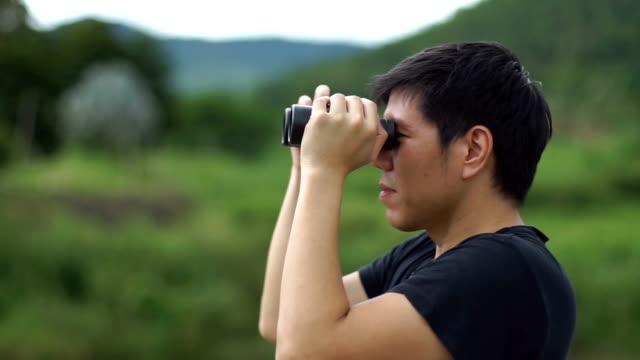 Man looking through binoculars in nature mountain background video