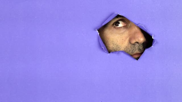 Man Looking Through Colorful Torn Paper