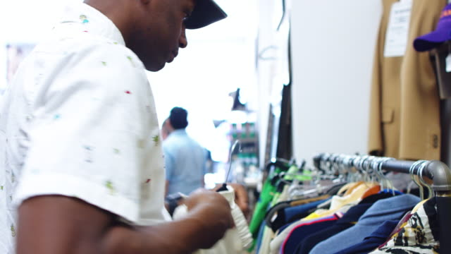 Man Looking Through Jackets in Second Hand Clothing Store video