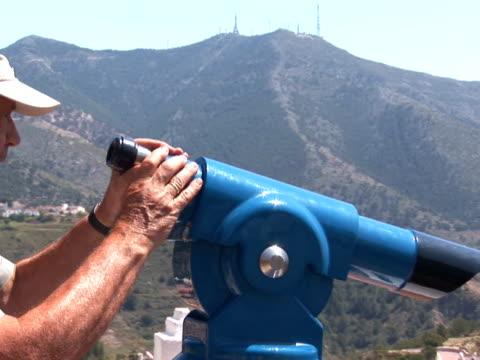 vídeos de stock e filmes b-roll de homem olhando através de telescópio - acessório financeiro