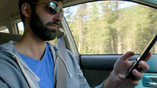 Man looks at his phone while driving video
