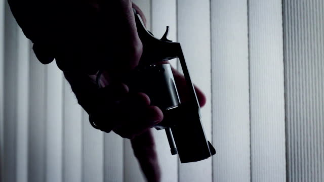 Man looks at loaded revolver in silhouette lighting inside video