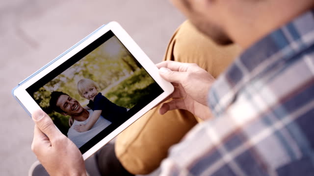 Man Looks At Photos Of Him And Son On Tablet video