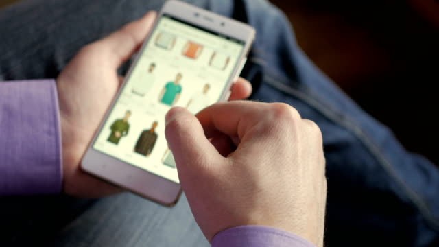 A man looks at the goods in the online clothing store. People using Smartphone, online shopping. The screen is blurred. Close-up. 4K UHD. A man looks at the goods in the online clothing store. People using Smartphone, online shopping. The screen is blurred. Close-up. 4K UHD. shopping online stock videos & royalty-free footage