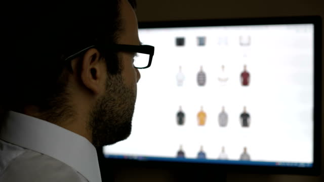 A man looks at the goods in the online clothing store, sitting at the desk. Computer online shopping . PC monitor showing blur feed page .