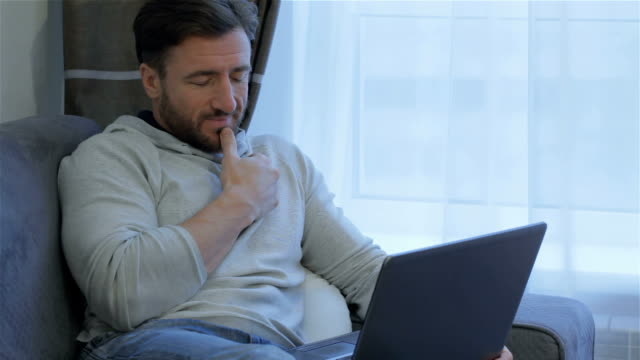 Man looks at the laptop screen at home video