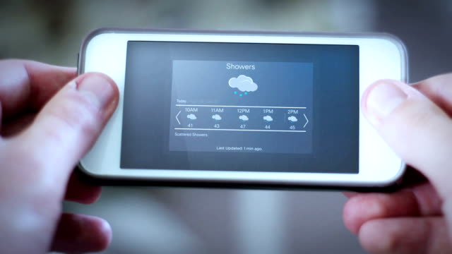 Man looks down at smartphone app with a weather app interface - Rain Showers video