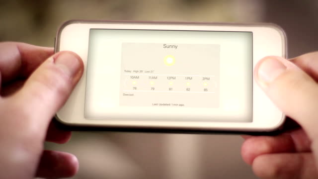 Man looks down at smartphone app with a weather app interface - Sunny hot weather video