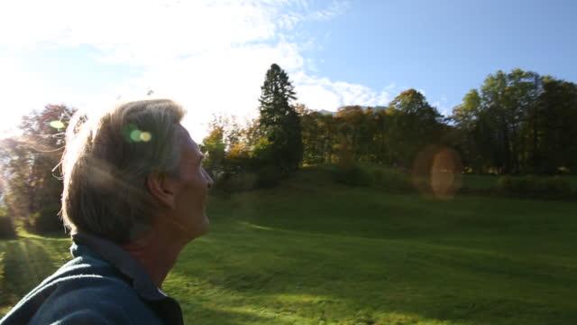 vídeos de stock e filmes b-roll de man looks off across autumn meadow, sunrise - man admires forest