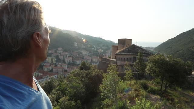 man looks over treed hill crest and village at sunrise - solo un uomo maturo video stock e b–roll