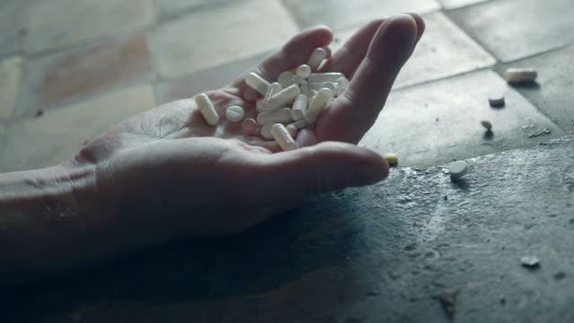 stockvideo's en b-roll-footage met man bewustzijn te verliezen of te sterven aan een overdosis drugs. hand met pillen closeup - amfetamine