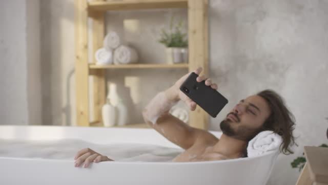 stockvideo's en b-roll-footage met mens die in badkuip ligt en telefoongesprek beantwoordt - cell phone toilet