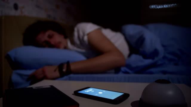 uomo sdraiato a letto spegnendo una sveglia al mattino - sonnecchiare video stock e b–roll