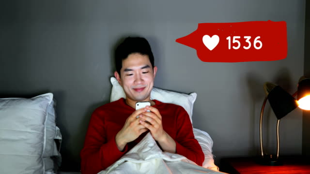 man lying in bed while checking his social media account 4k - rappresentazione umana video stock e b–roll
