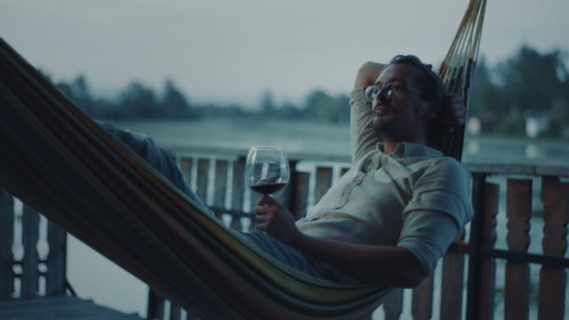 vidéos et rushes de homme se trouvant dans le hamac et buvant le vin - man drinking terrace