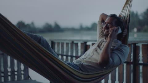vídeos y material grabado en eventos de stock de hombre acostado en hamaca y hablando por teléfono - actividades recreativas