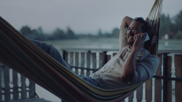Man lying in hammock and talking on the phone video
