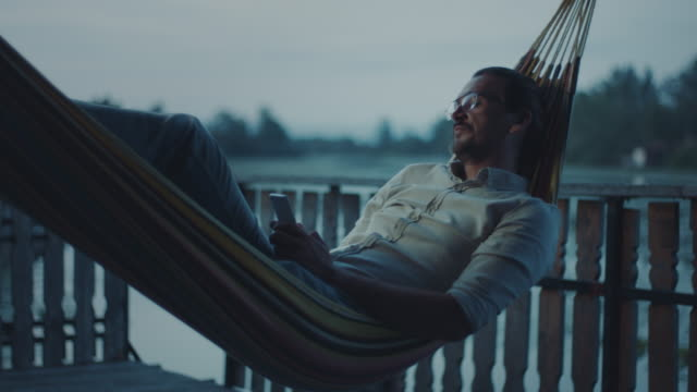 Man lying in hammock and texting