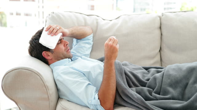 Man lying on the couch sick with a temperature video