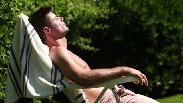 mann liegt am sommertag beim sonnenbaden im freien - sonnenbaden stock-videos und b-roll-filmmaterial