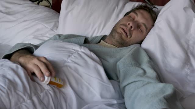 mann liegt bewusstlos im bett fallen eine pille flasche - suchtkranker stock-videos und b-roll-filmmaterial