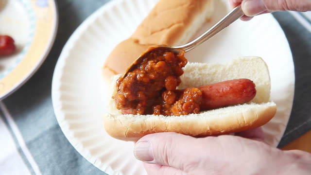 man makes a chili dog - chilli con carne video stock e b–roll