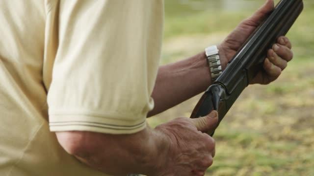 vidéos et rushes de homme fait un tir d'un fusil de chasse - armement