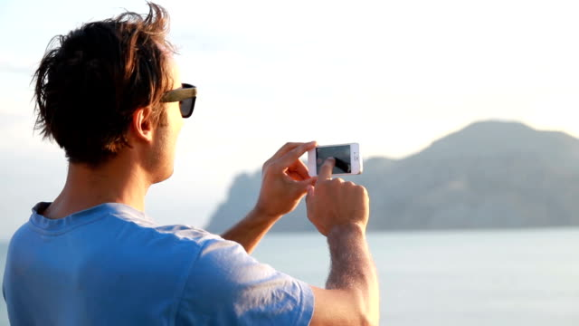 man makes a video panorama in the mountains on the phone video