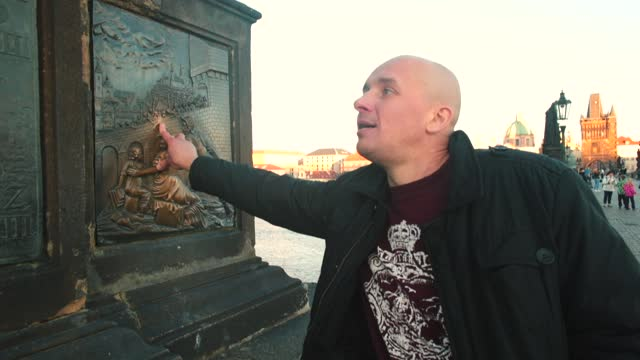 Man makes a wish at famous place on Charles Bridge. Touch and rub for good luck.