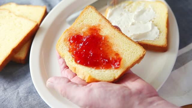 Man makes cream cheese and jam sandwich