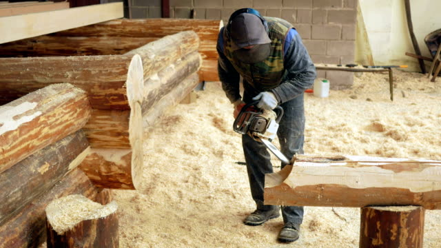 man makes curly cutting wood chainsaw. the log will be part of the future of the wooden house. protective face mask on the face of the builder and a lot of sawdust - motosega video stock e b–roll