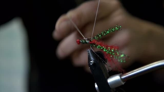 ein mann macht angeln fliegen. ausrüstung zum stricken von fliegen und materialien zur vorbereitung auf das fliegenfischen. - fischköder stock-videos und b-roll-filmmaterial