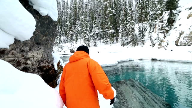 vídeos de stock e filmes b-roll de man makes his way along a snowy path on waters edge - man admires forest