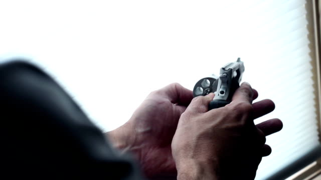Man makes sure his revolver is unloaded inside - reverse angle video