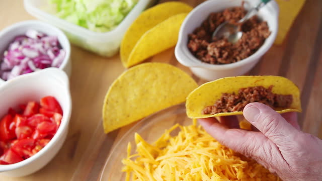 Man makes tacos from overhead Older man prepares a taco with tomatoes, onions, lettuce, ground beef and grated cheese ground beef stock videos & royalty-free footage